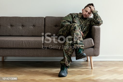 istock Helpless soldier sitting on a couch while waiting for a therapy session 1014213066