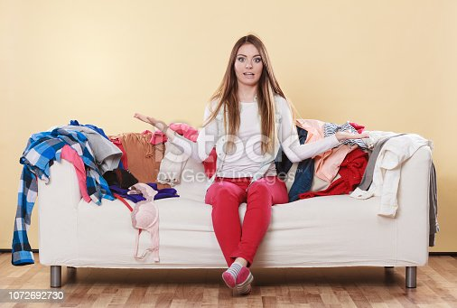 460589747istockphoto Helpless woman sitting on sofa in messy room home. 1072692730