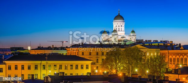 The iconic domes and white towers of Helsinki Cathedral overlooking the Government quarter palaces and offices illuminated under deep blue dusk skies in the heart of central Helsinki, Finland's vibrant capital city.
