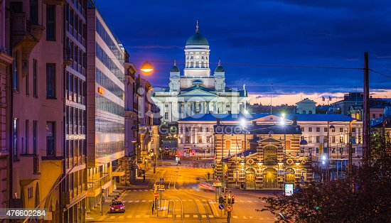 The iconic domes and white marble facade of Helsinki Cathedral spotlit and the deep blue dusk skies of a summer sunset overlooking the streetlights and tramlines of Market Square in the heart of Finland's picturesque capital city. ProPhoto RGB profile for maximum color fidelity and gamut.