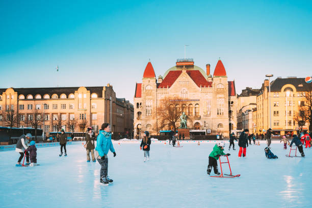 Helsinki, Finland. Children Skating On Rink On Railway Square On Background Of Finnish National Theatre In Winter Sunny Day stock photo
