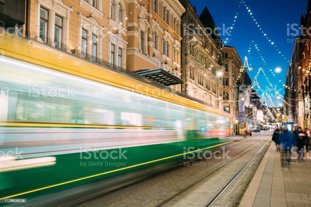 Helsinki, Finlandia. Tranvía sale en desenfoque de movimiento de parada en la calle Aleksanterinkatu en Distrito de Kluuvi de noche Navidad Navidad año nuevo fiestas iluminación de noche - Foto de stock de Aire libre libre de derechos