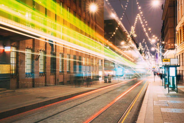 helsinki, finland. tram departs in motion blur from stop on aleksanterinkatu street in kluuvi district in evening night christmas xmas new year festive illumination - stop motion stock photos and pictures