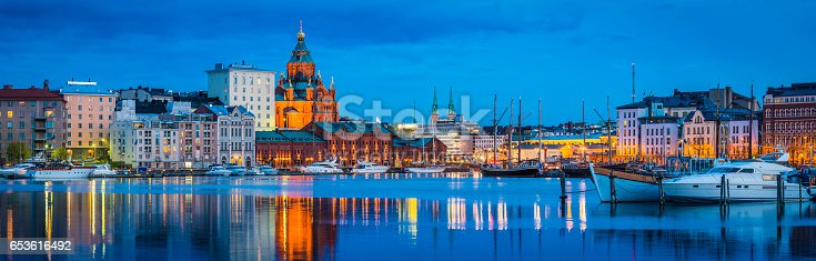 The iconic domes of Uspenski Cathedral overlooking the redeveloped warehouses, restaurants and waterfront apartments of Katajanokka and the boats moored in the tranquil blue waters of the north habour in the heart of Helsinki, Finland's vibrant capital city.