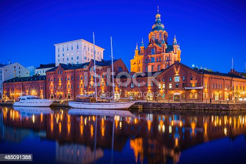The iconic domes of Uspenski Cathedral overlooking the redeveloped warehouses, restaurants and waterfront apartments of Katajanokka and the boats moored in the tranquil blue waters of the north habour in the heart of Helsinki, Finland's vibrant capital city. ProPhoto RGB profile for maximum color fidelity and gamut.