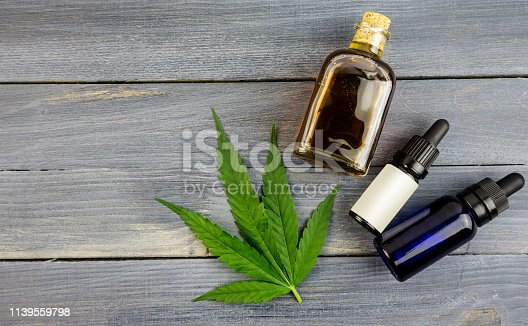 Hemp leaf on wooden table, cannabis oil extracts in bottles