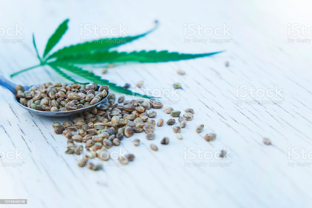 hemp leaves on wooden background, seeds, cannabis oil extracts in jars stock photo