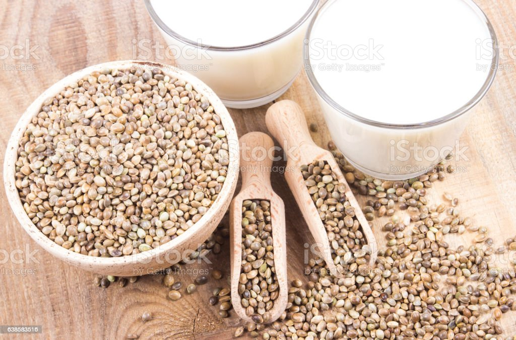 Hemp milk, seeds on wooden background . Close Up . stock photo