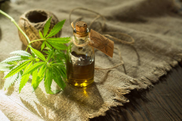 Hemp oil, canvas and threads on a dark wooden surface stock photo