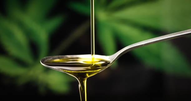 CBD hemp oil dropping on spoon stock photo