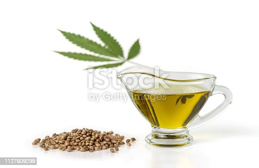 Hemp oil in a glass gravy boat with a bunch of marijuana seeds and a marijuana leaf. Isolated on white background.