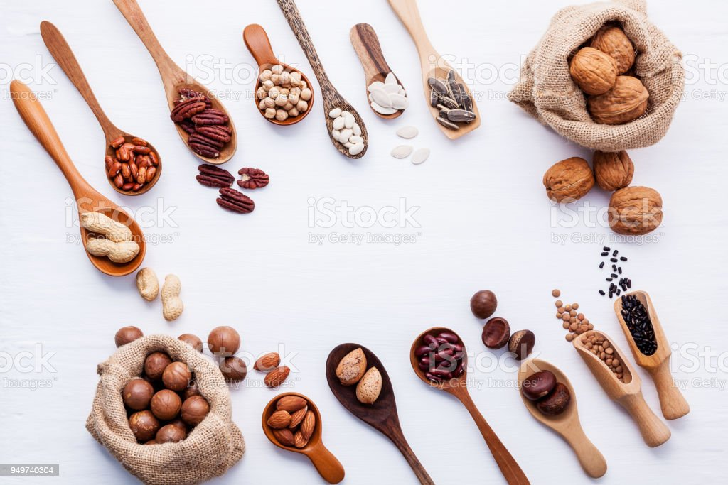 Hemp Sack bags and spoon of various legumes and different kinds of nuts walnuts kernels ,hazelnuts, almond kernels,brown pinto ,red kidney beans and pecan set up on white wooden table. stock photo