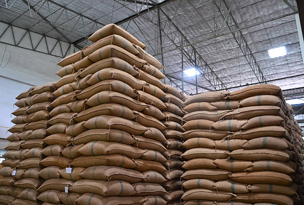 hemp sacks stacked high in a large warehouse - sack stock pictures, royalty-free photos & images