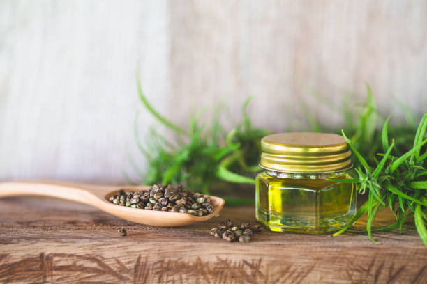 hemp seeds and hemp oil in a glass jar on a green marijuana leaf background. medical marijuana concept, cbd cannabis oil. - dieta macrobiotica foto e immagini stock