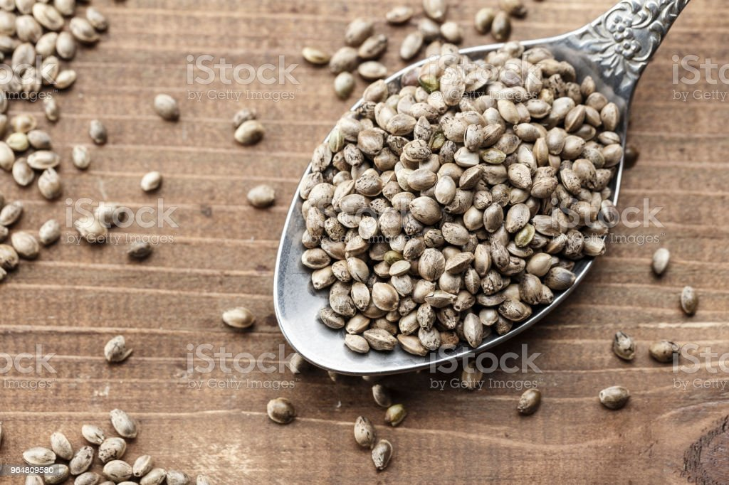 hemp seeds in a metal spoon on a wooden background royalty-free stock photo