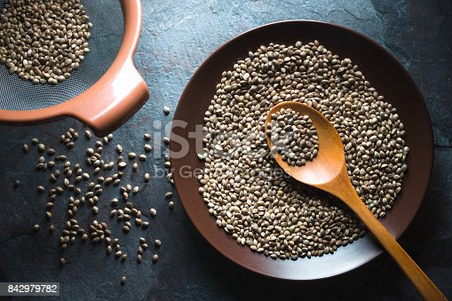 istock Hemp seeds on a plate and in a sieve on a gray blue stone 842979782