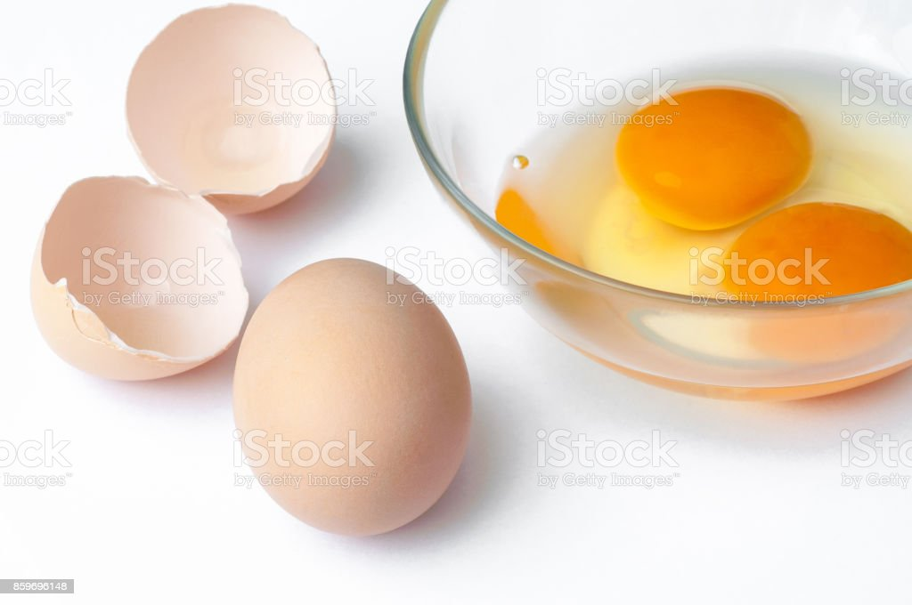 hen egg, eggshell and Raw egg yolk in glass closeup isolated on white background stock photo