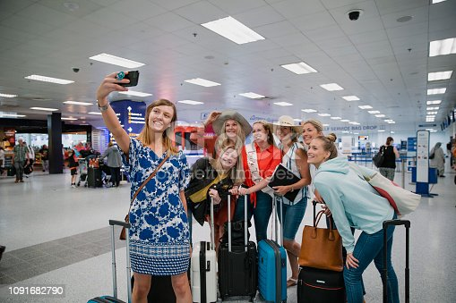 Mixed-age hen party are taking a selfie on a smart phone in the airport terminal.