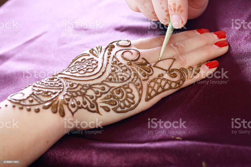 henna being applied stock photo