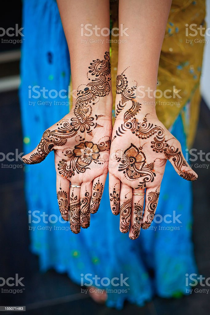 Henna on both hands of Indian woman wearing sari stock photo