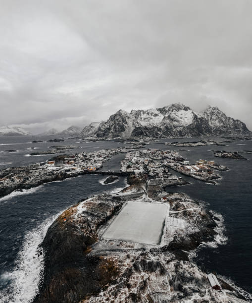 Henningsvær soccer field at winter covered with snow with outstanding mountain on horizon. Lofoten Islands, Norway. stock photo