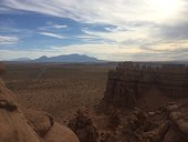 On the road to Lake Powell, view of goblin hoodoo formations with highway and Henry Mountain range in the background