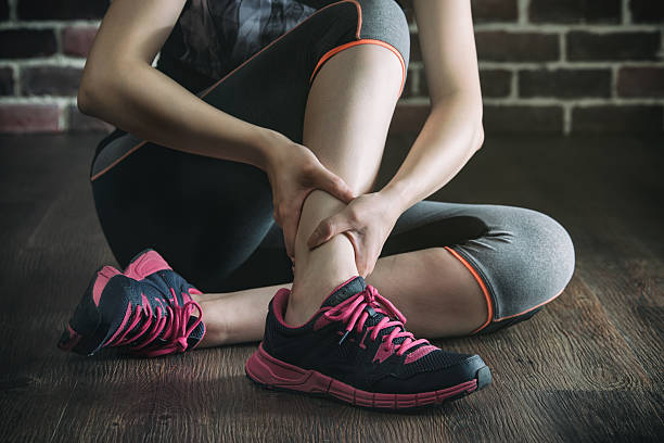 her ankle injured in gym fitness exercise training, healthy - caviglia foto e immagini stock