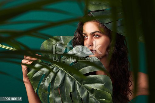 Cropped shot of a beautiful young woman posing with monstera leaves against a green background