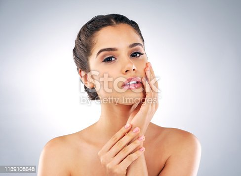 Studio portrait of a beautiful young woman with gorgeous skin holding her face against a grey background