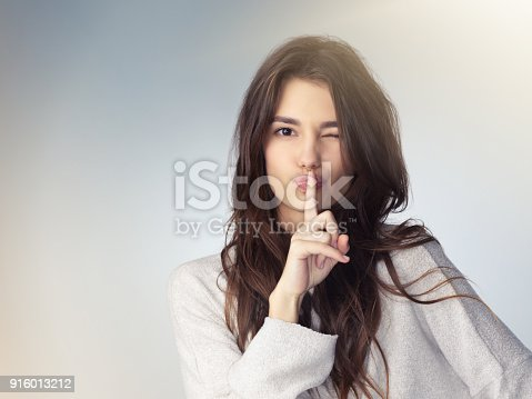 Studio shot of a beautiful young woman posing against a gray background