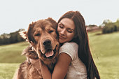 Beautiful young woman keeping eyes closed and smiling while embracing her dog outdoors