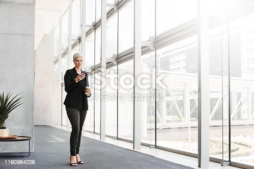 Shot of a mature businesswoman using a smartphone in a convention centre