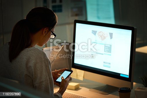 Shot of a young designer using a cellphone while working on a computer in an office at night