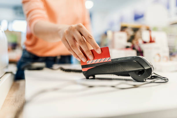 Her credit card's got her shopping covered Customer paying with contact less card. NFC technology payment in store. Close Up. Shopping in pharmacy. Photo of a client is paying using red credit card. Close up of human hand putting or Swiping credit card into payment machine in drug store smart card stock pictures, royalty-free photos & images