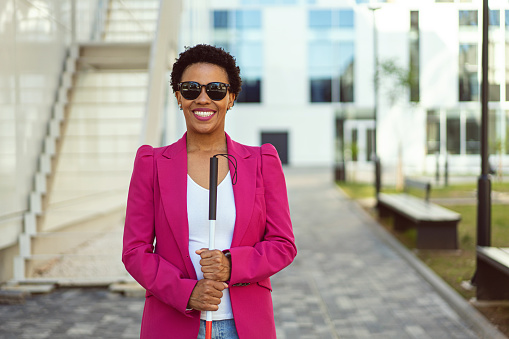 Portrait of a confident and cheerfulmixed-race businesswoman, with visual impairment, standing in front of her corporate building while holding blind person cane