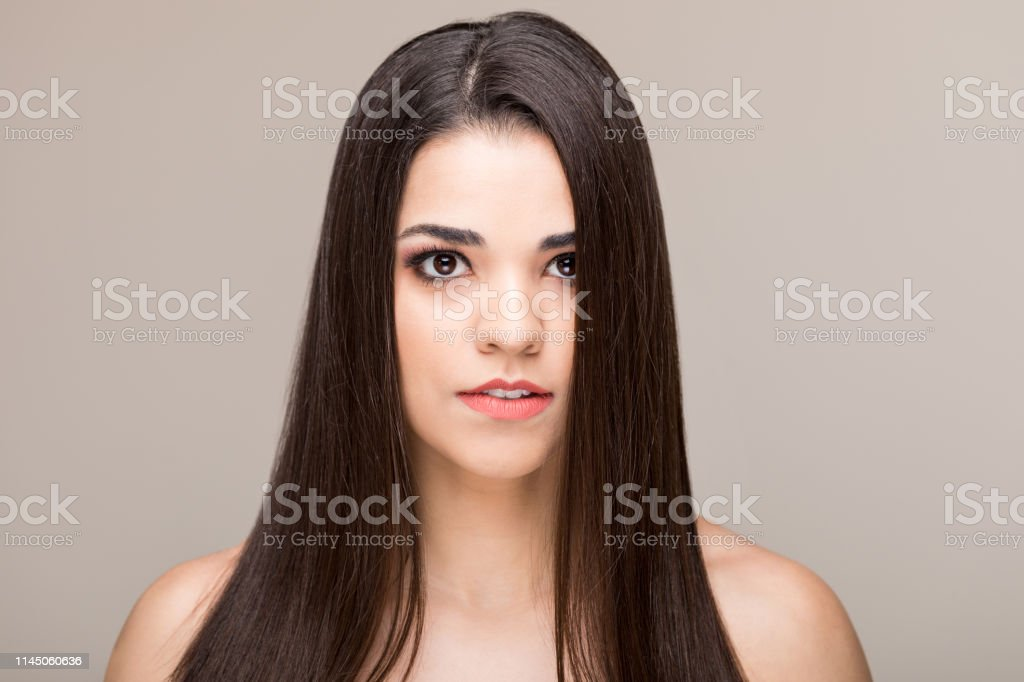 Closeup of attractive mid adult woman with long brown hair against...