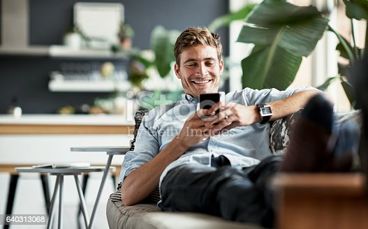 Shot of a happy young man using his cellphone while relaxing on the couch at home