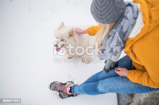 Above shot of a young woman sitting on the stone and cuddling her samoyed dog on the snowy mountain.