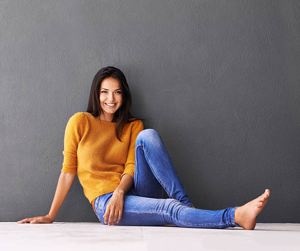 Her outfit matches her relaxed mood Portrait of an attractive young woman sitting on the floor against a grey wallhttp://195.154.178.81/DATA/i_collage/pi/shoots/783562.jpg skinny jeans stock pictures, royalty-free photos & images
