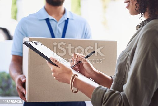 Closeup shot of a woman signing for her delivery from the courier