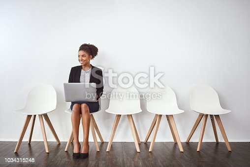 Studio shot of a young businesswoman using a laptop while waiting in line against a gray background