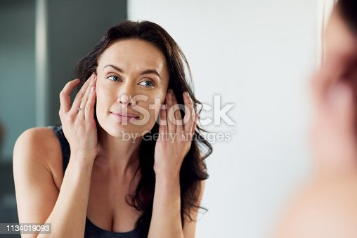 Cropped shot of an attractive woman admiring her face in the bathroom mirror