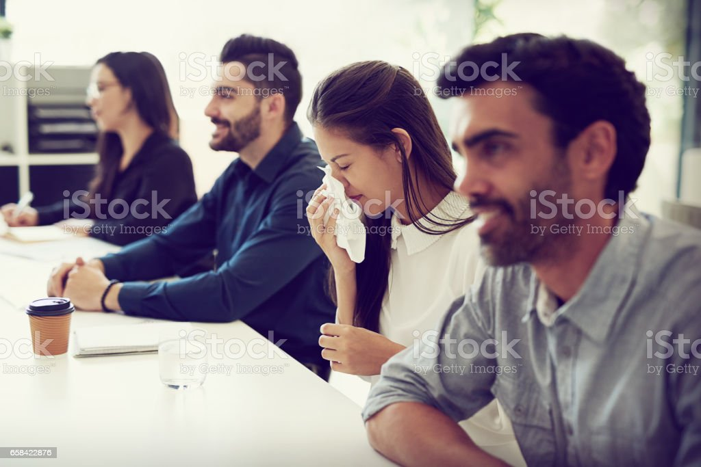 Her sneezes keep interrupting the meeting stock photo