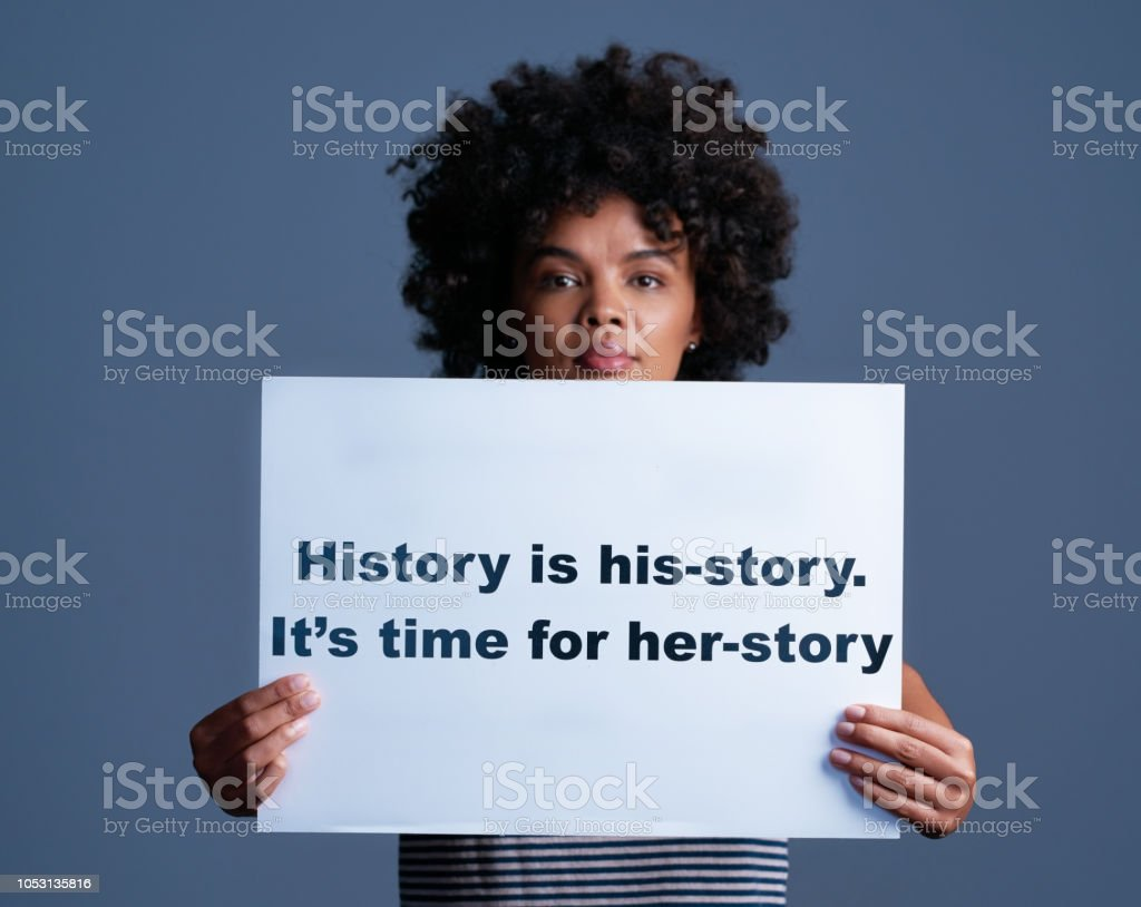 """Her story is part of his-story too Studio shot of a young woman holding a sign saying """"history is his-story. it's time for her-story"""" Adult Stock Photo"""