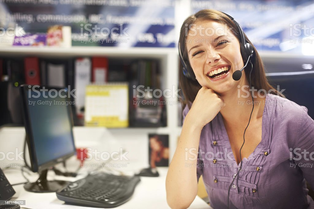Her sunny disposition can win over any client! A lovely young woman sitting behind her desk wearing a headset and laughing 20-24 Years Stock Photo