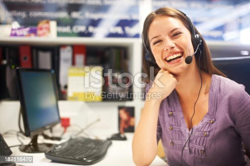 A lovely young woman sitting behind her desk wearing a headset and laughing