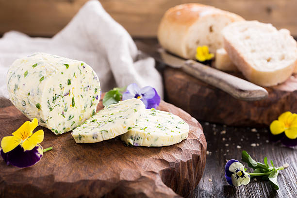 Herb butter with edible flowers on wooden cutting board stock photo