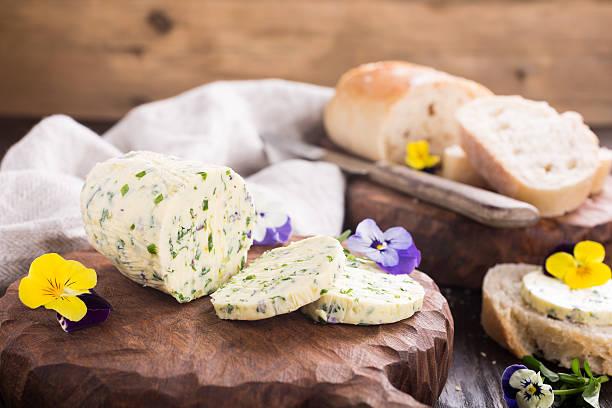 herb butter with edible flowers on wooden cutting board - kräuterfaltenbrot stock-fotos und bilder