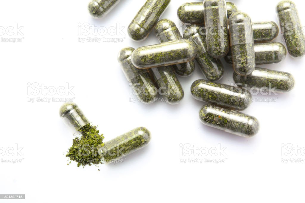 herb capsule from bottle on white background stock photo