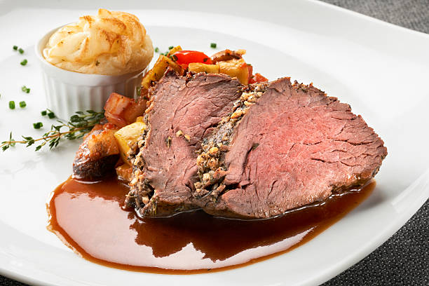 Herb Crusted Beef Tenderloin with saute vegetables Herb crusted beef tenderloin served with saute vegetables of onions, mushrooms, squash, and red bell peppers, a souffle of mashed potatoes, and a light gravy. burwellphotography stock pictures, royalty-free photos & images